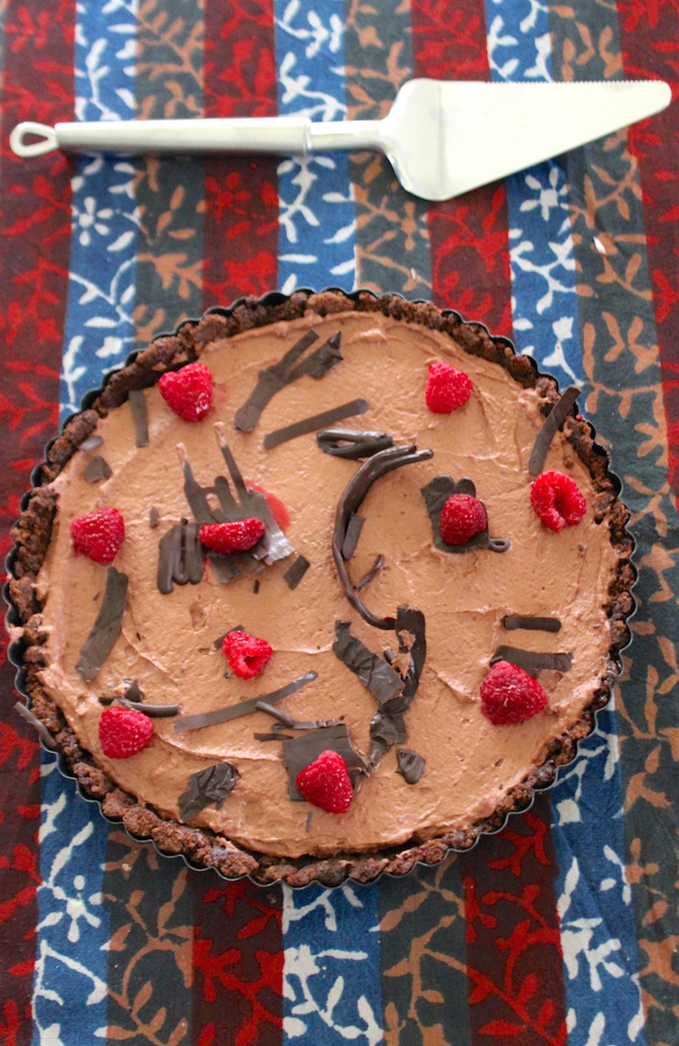 A tart made with a chocolate cookie crust, layered with easy chocolate mousse and scattered with raspberries. Get the recipe on Hot Chocolate Hits!