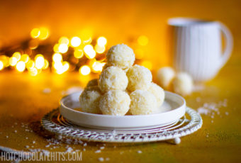 A stack of the coconut balls, with a cup of tea.